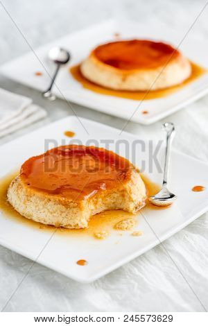 Two Plates With Creme Caramel On A White Tablecloth