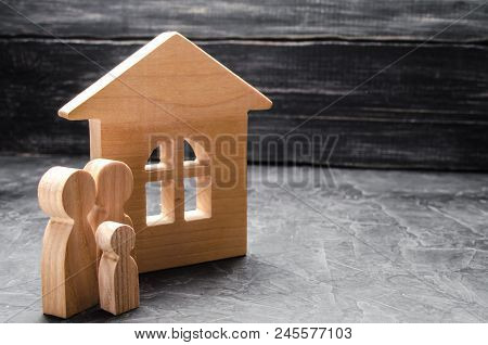 Wooden Figures Of The Family Stand Near A Wooden House. The Concept Of Finding A New Home, Moving. A