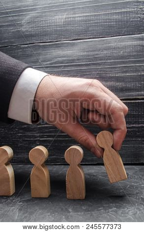 The Hand Of A Businessman Puts A Wooden Figure Of A Man In A Row To Other Employees. The Concept Of