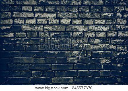 Old Shabby Dark Brick Wall. Aged Weathered Sloppy Brickwork. Retro Grunge Background