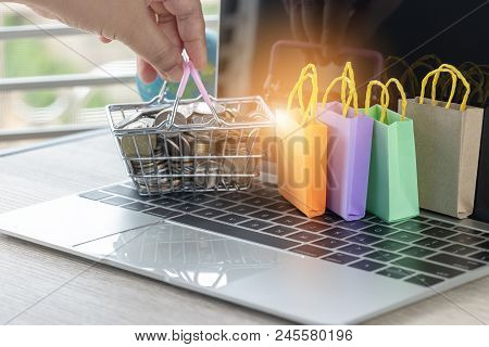 Hand Holding Basket Of Thai Coins And Shopping Bags On Laptop Keyboard With Globe Nearby. Consumer C