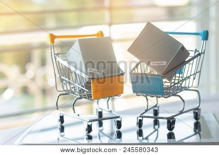 Cardboard Boxes In Trolley On Tablet. Consumers Can Buy Products Directly From Seller Over Internet
