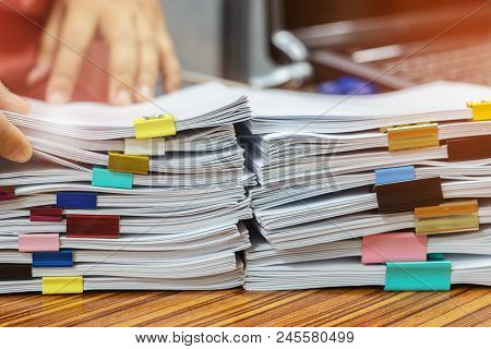 Businessman Hands Working In Pile Of Unfinished Paperwork For Searching Information On Desk Office.