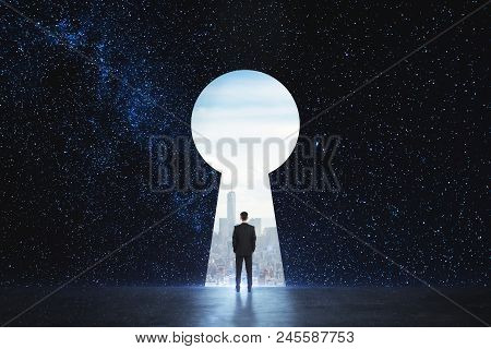 Back View Of Young Businessman Standing Against Keyhole Door On Starry Sky Background. Dream, Succes