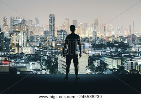 Back View Of Young Man On Rooftop Looking At Illuminated Night City. Research And Success Concept