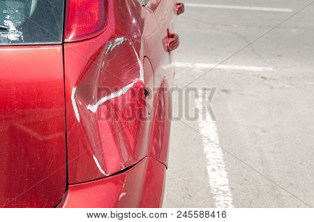Red Scratched Car With Damaged Paint In Crash Accident Or Parking Lot And Dented Damage Of Metal Bod