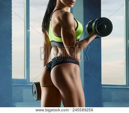 Photo Of Strong Fit Model Training In Gym , Doing Fitness Exercises With Heavy Dumbbells. Having Ath