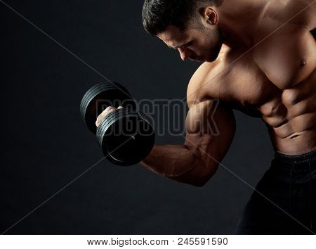 Cropped Frontview Of Strong Bodybuilder With Clear Muscular Relief Lifting Heavy Dumbbell In Gym. Sp