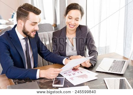 Cheerful Professional Multiethnic Analysts In Formalwear Discussing Statistics While Viewing Report