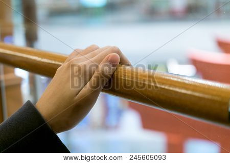 A Young Girl Hold The Wooden Banister With Loneliness Mood.