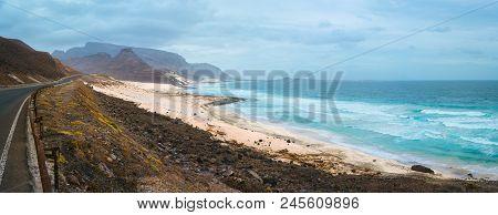 Road Along Atlantic Coastline White Sand Dunes And Ocean Waves Rolling. Road Leads Between Black Vol