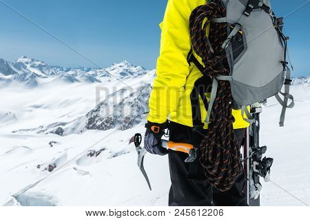 A Mountaineer Man Holds An Ice Ax High In The Mountains Covered With Snow. Close-up From Behind. Out