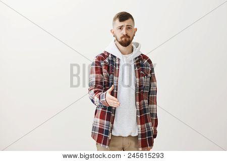 Studio Shot Of Gloomy Unconfident European Guy With Fair Hair In Trendy Plaid Shirt Over Hoodie, Pul