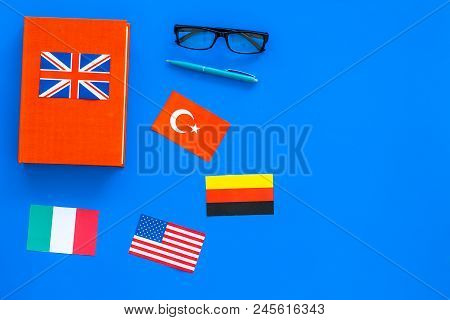 Language Study Concept. Textbooks Or Dictionaries Of Foreign Language Near Flags On Blue Backgrond T