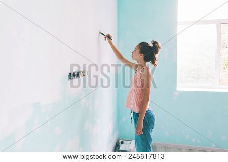 Preteen child painting the wall in her room in blue and white colors. Young girl making interior renovation at home. poster