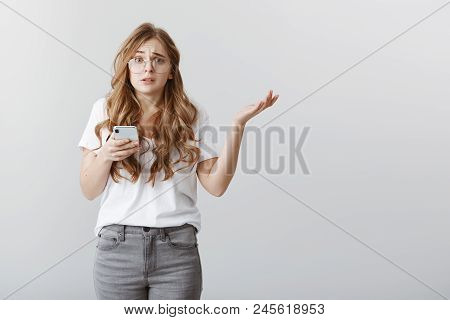 Girl Is Clueless Who Sent Ridiculous Message. Portrait Of Worried Confused Attractive Woman With Blo