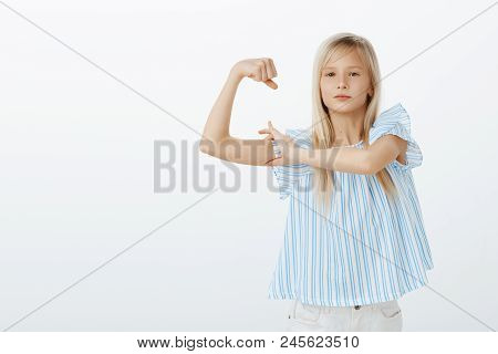 Maybe I Am Small But Strong. Portrait Of Proud Confident Young Blond Girl In Stylish Blouse, Raising