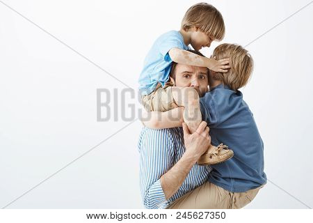 Close-up Shot Of Tired Worried Father Holding Little Son On Shoulders While Older Son Hanging On Che