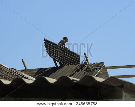 The roofer carries slate on the roof. Roof dismantling poster