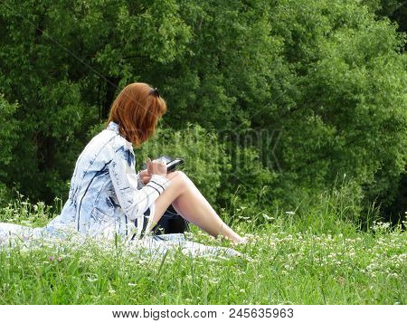 Young Woman Sitting On The Grass With A Smartphone In A Summer Park. Communication, Online Dating, S
