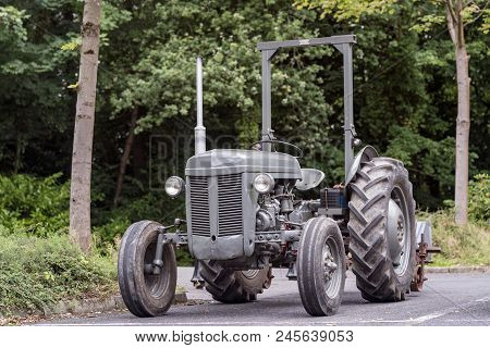 A Very Old Grey Tractor On A Road.