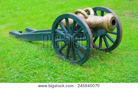 An ancient cannon against a green grass background