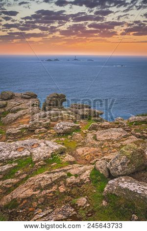 Large Boulders On The Coast And Small Lighthouse On The Background In The Lands End - The Most Weste