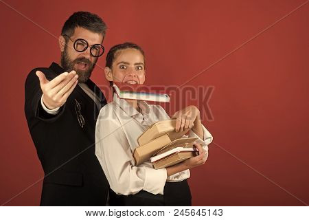 Teenager And Tutor With Glasses Hold Pile Of Books And Book In Teeth. Back To School Concept. Girl A