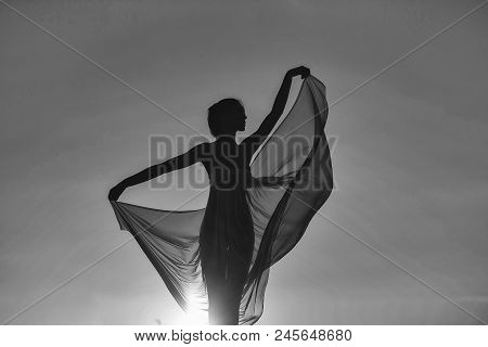 Performance Against The Sun. Silhouette Of Slim Girl Young Woman Female Model Dances In Transparent