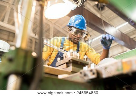 Serious Busy Young Black Factory Engineer In Hardhat And Safety Goggles Examining Milling Lathe And