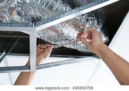 Male technician repairing industrial air conditioner indoors