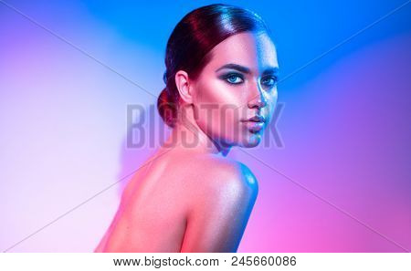 High Fashion model girl in colorful bright sparkles and neon lights posing in studio, portrait of beautiful woman, trendy glowing make-up. Art design colorful make up. Glitter Vivid neon makeup