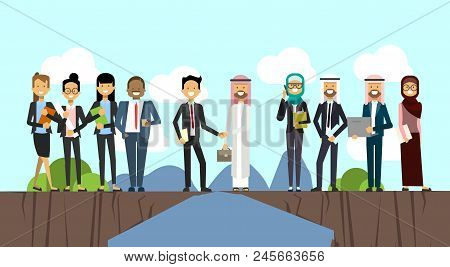Businessman In Business Suit Shaking Hands Arabic Man Traditional Clothes Over Chasm Between Mountai