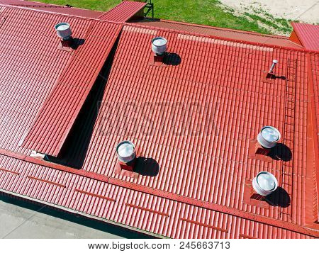New Red Metal Warehouse Roof With Installed Pipes Of Ventilation Systems. Aerial Photo