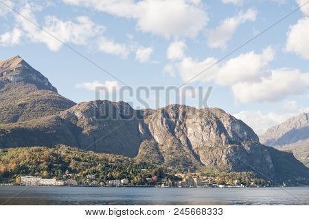 Panorama of Como Lake, Italy. View of Shoreline with Old Houses and Mountains.
