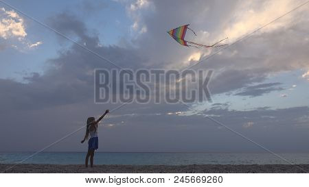 Child Playing Flying Kite On Beach At Sunset, Happy Little Girl On Coastline