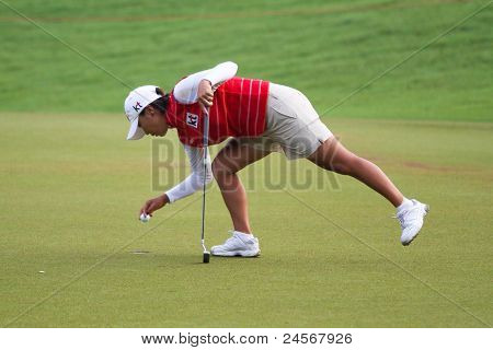 KUALA LUMPUR, MALAYSIA - OCTOBER 16: Mi Hyun Kim of South Korea collects the ball after her putt at the Sime Darby LPGA Malaysia 2011 golf tournament on Oct 16, 2011 in Kuala Lumpur, Malaysia.