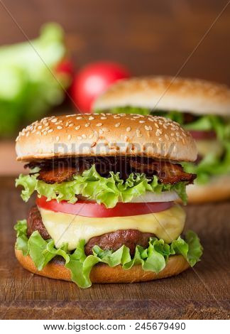 Fresh Burger With Cheese And Bacon On Wooden Table