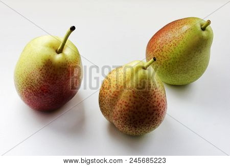 Three Juicy Ripe Golden Pears With Amazing Shadows On A White Table. Selective Soft Focus And Space