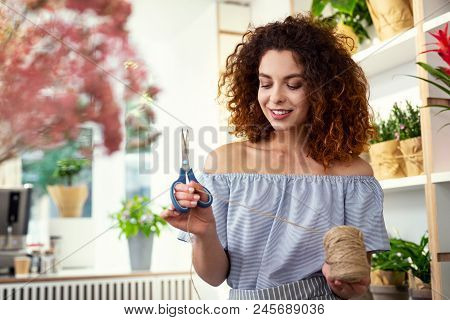 Floristic Design. Nice Pleasant Woman Cutting A Piece Of Rope While Working On A Floristic Design