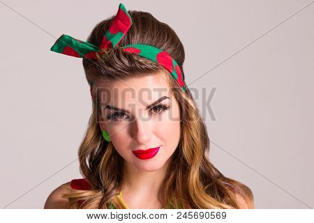 Woman with hairdo and make up poses in studio, pin up style, close up portrait poster