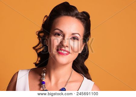 Brunette with hairdo and make up poses in studio, pin up style, close up portrait poster