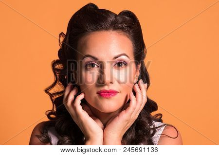 Beautiful brunette with hairdo and make up poses in studio, pin up style, close up portrait poster