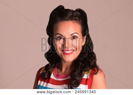 Happy Brunette With Hairdo And Make Up Smiles In Studio, Pin-up Style, Close-up Portrait
