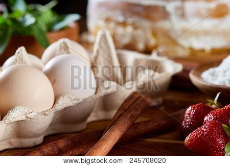 Top View Raw Ingredients For Cooking Strawberry Pie Or Cake On Wooden Table: Eggs, Sugar, Mint And S