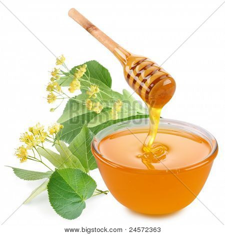 Linden honey is pouring with sticks in a jar. Next to them are linden flowers. Isolated on white background.