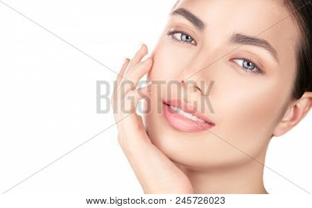Beautiful Spa Brunette girl Touching her Face. Perfect Fresh Skin. Beauty Portrait. Pure Beauty Model young Woman. Youth and Skin Care Concept. Acne treatment, cleansing. Isolated on white background