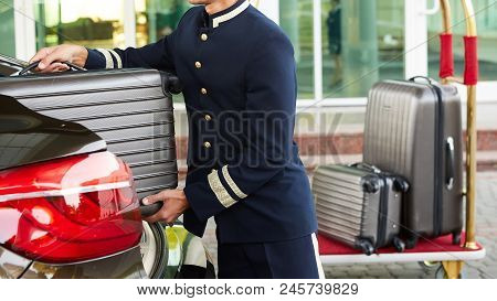 Bellboy Taking Baggage Of Guest From Thee Car To His Room.