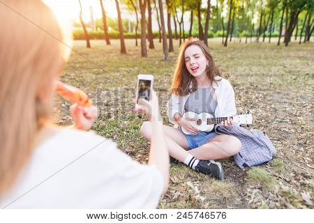 Girl Takes A Camera On The Smartphone As A Girlfriend Plays Ukulele In The Park. The Girl Takes The