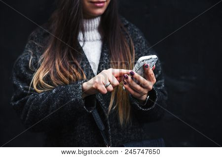 Happy Beautiful Woman Speaking On Mobile Phone On A Black Background